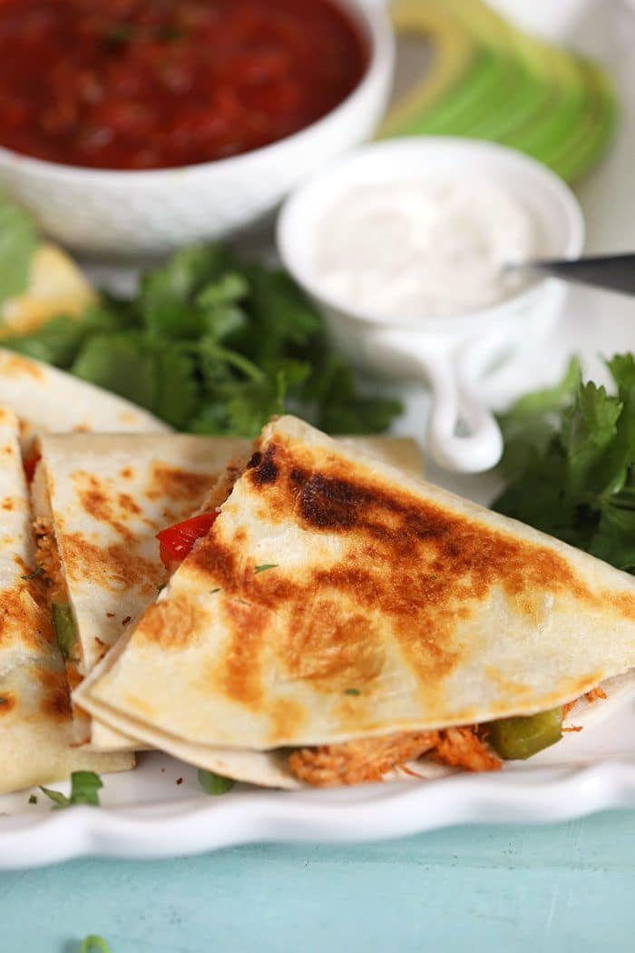 chicken quesadilla on a white plate with cilantro and sour cream.