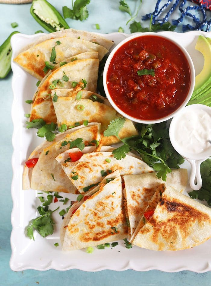 Overhead shot of chicken quesadillas on a square white platter with salsa.