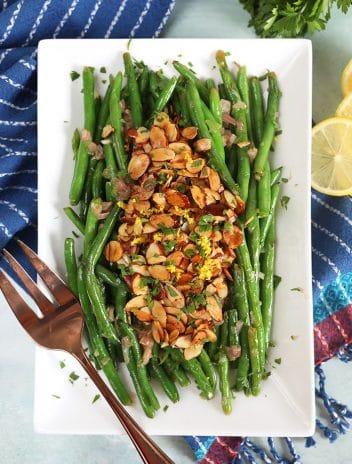 Overhead shot of green beans almondine on a white platter.