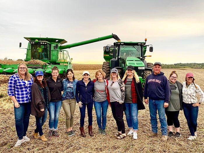 a line of people in a corn field standing in front of a combine.