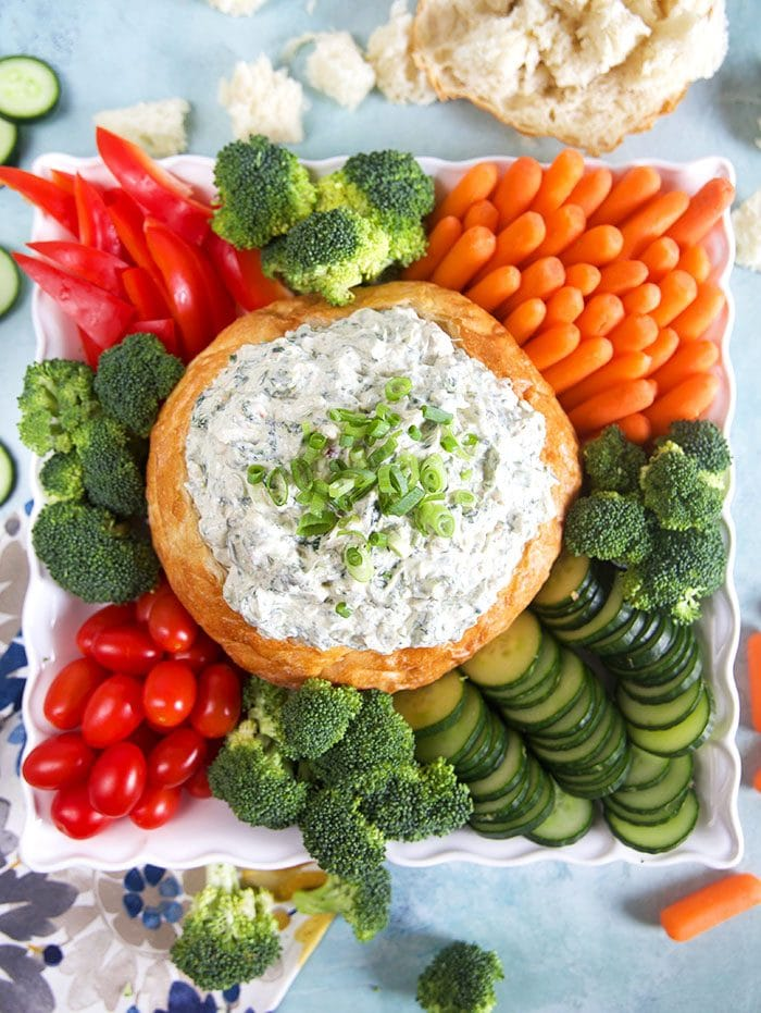 Overhead shot of knorr spinach dip in a bread bowl with vegetables around the bottom on a white square platter.