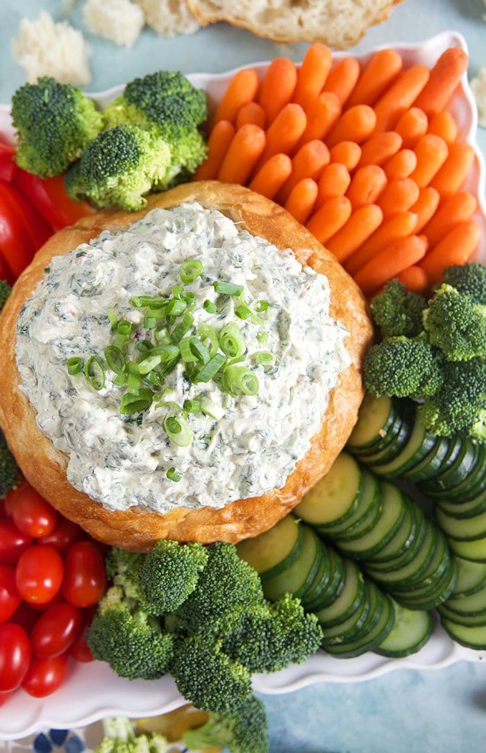 Overhead shot of Knorr Spinach Dip in a bread bowl with vegetables on a platter.