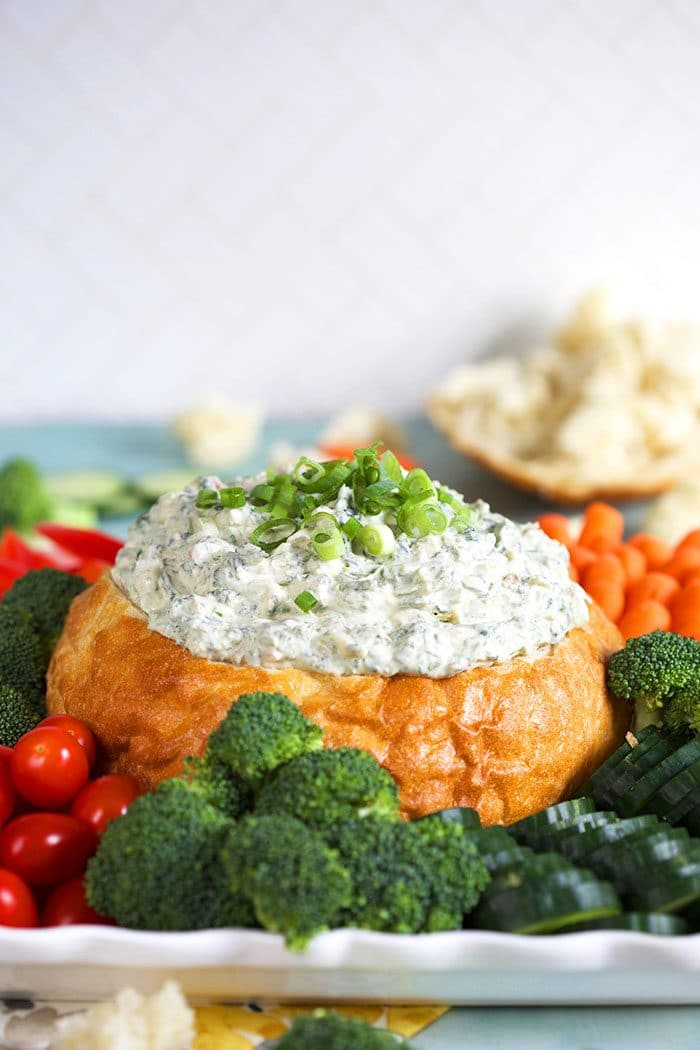 Knorr Spinach Dip in a white bread bowl with vegetables around the bottom.