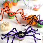 Play Doh spiders on a white background with pumpkins.
