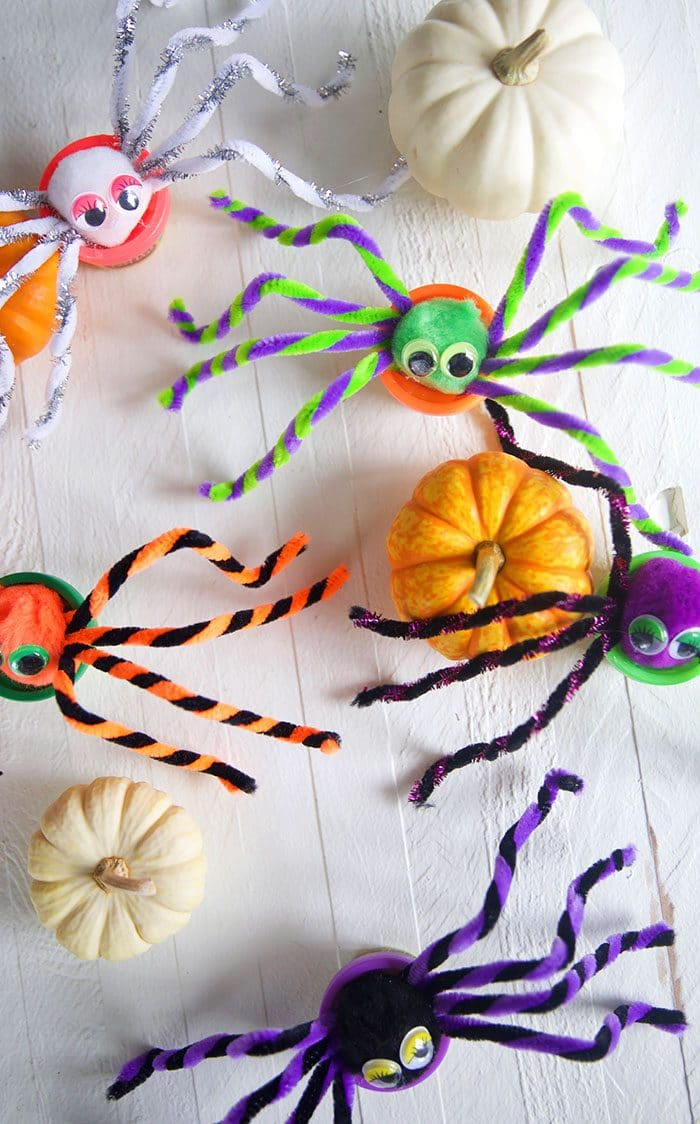 Overhead shot of Play doh spiders on a white background.