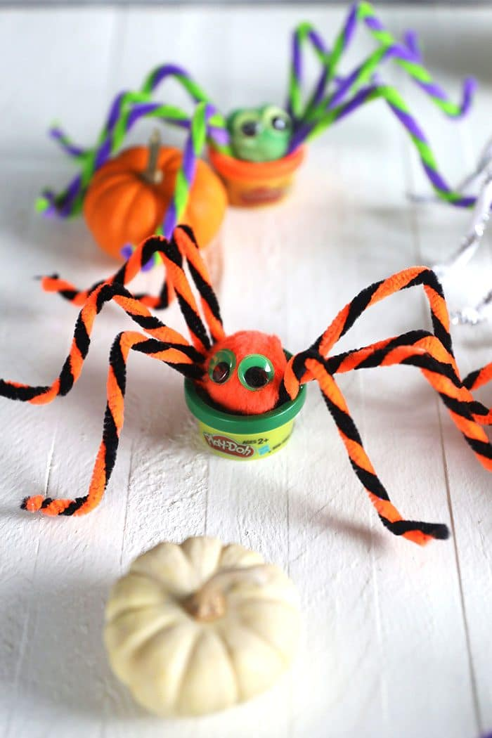 Play doh spiders on a white background with a white pumpkin.