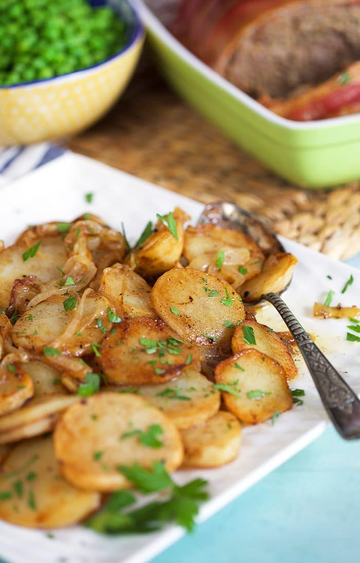 Lyonnaise potatoes on a white platter with a spoon and peas in the background.