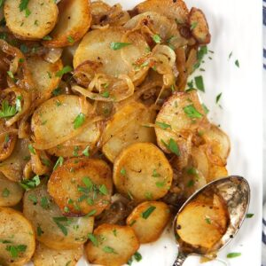 overhead shot of lyonnaise potatoes on a white square platter with a patina'd spoon.