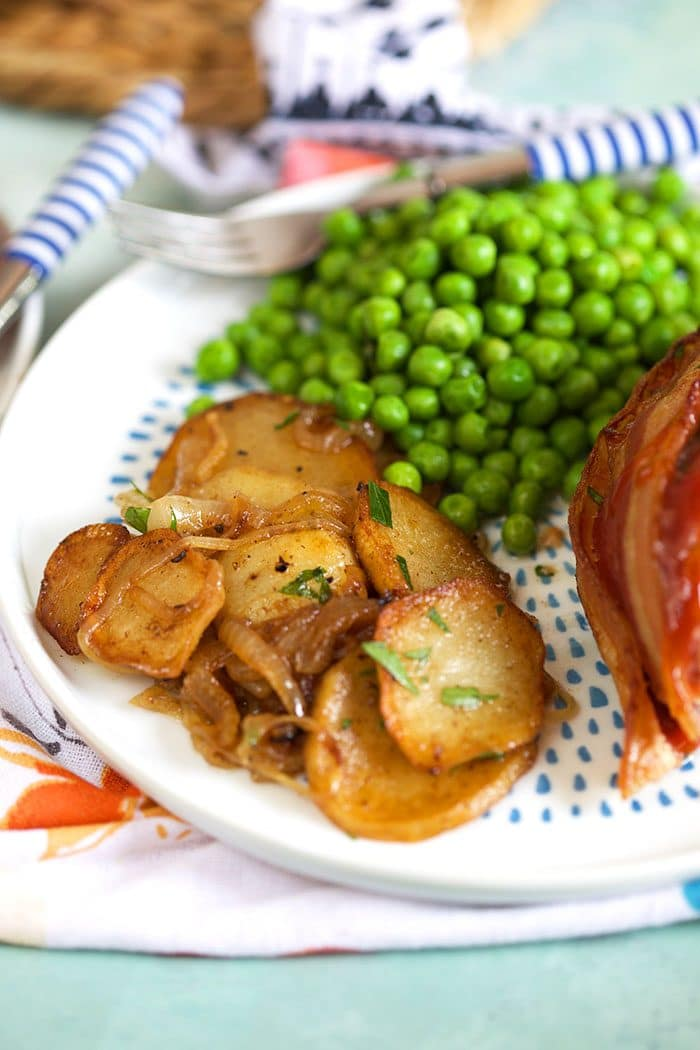 Lyonnaise potatoes on a white plate with peas and meatloaf.