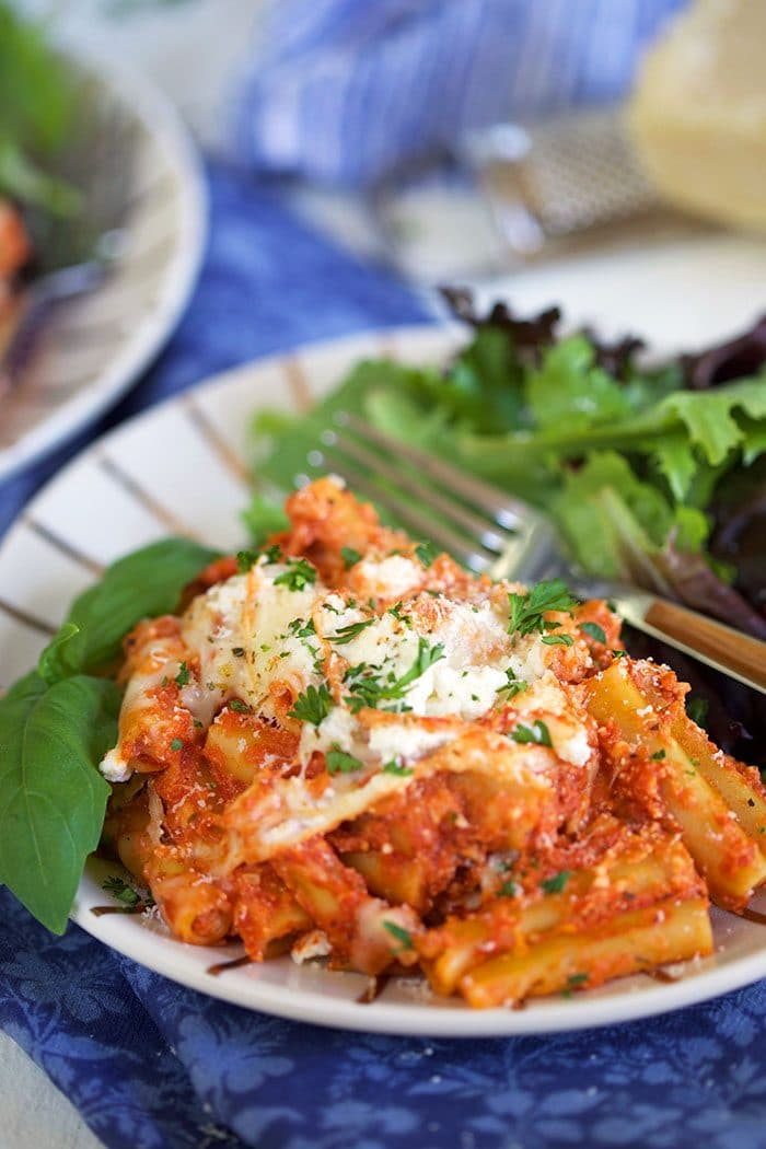 Close up of slow cooker baked ziti on a plate with a green salad.