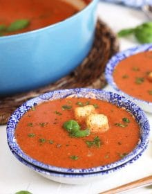 Tomato Basil Bisque in a blue and white bowl with croutons and basil on a white background.