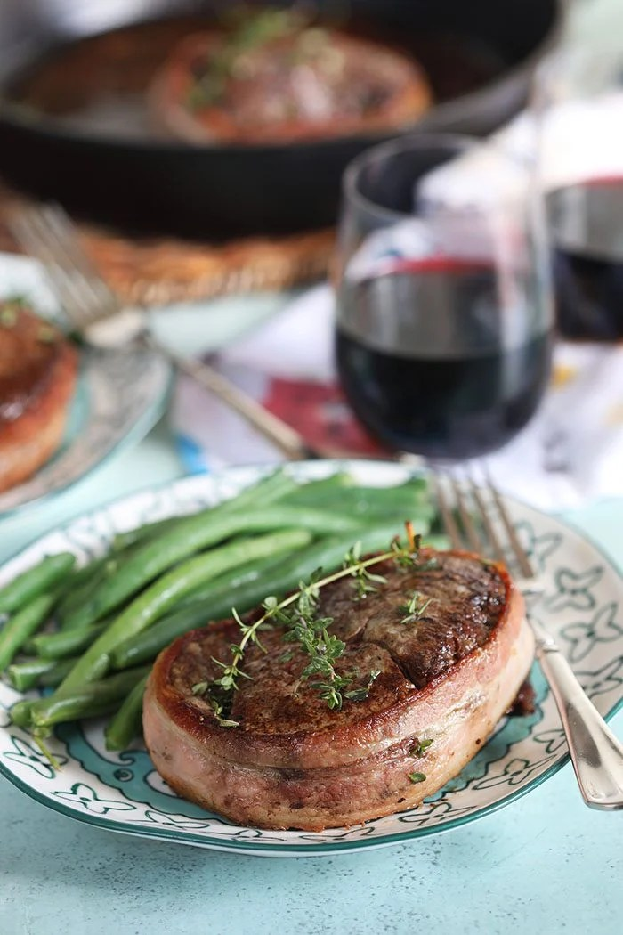 Bacon wrapped filet mignon on a plate with green beans and a glass of wine in the background.
