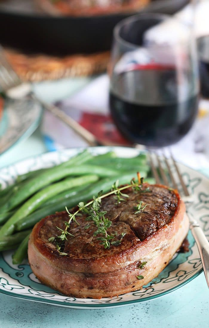 Bacon wrapped filet mignon on a plate with a green beans and a fork.