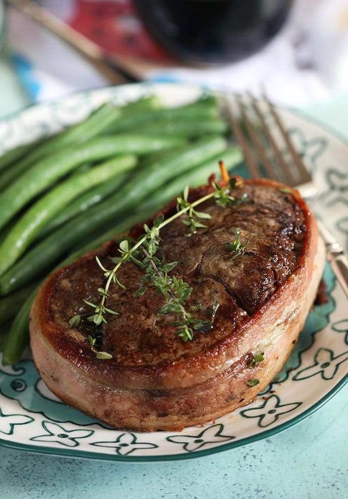 Bacon wrapped filet mignon with thyme sprigs on top and green beans on the plate.