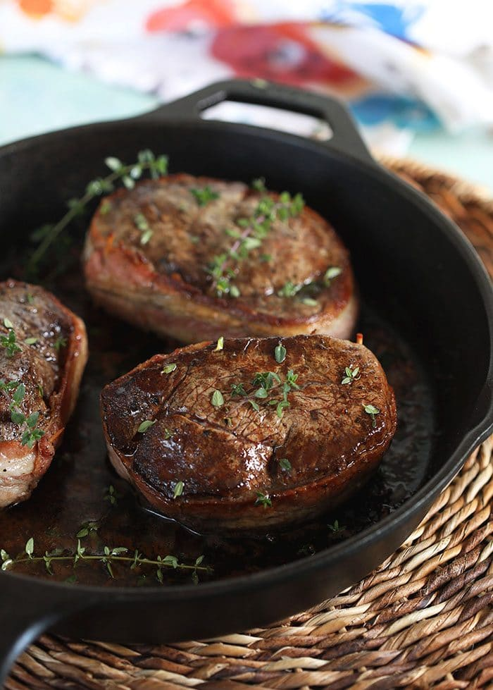 Bacon wrapped filet mignon in a cast iron skillet