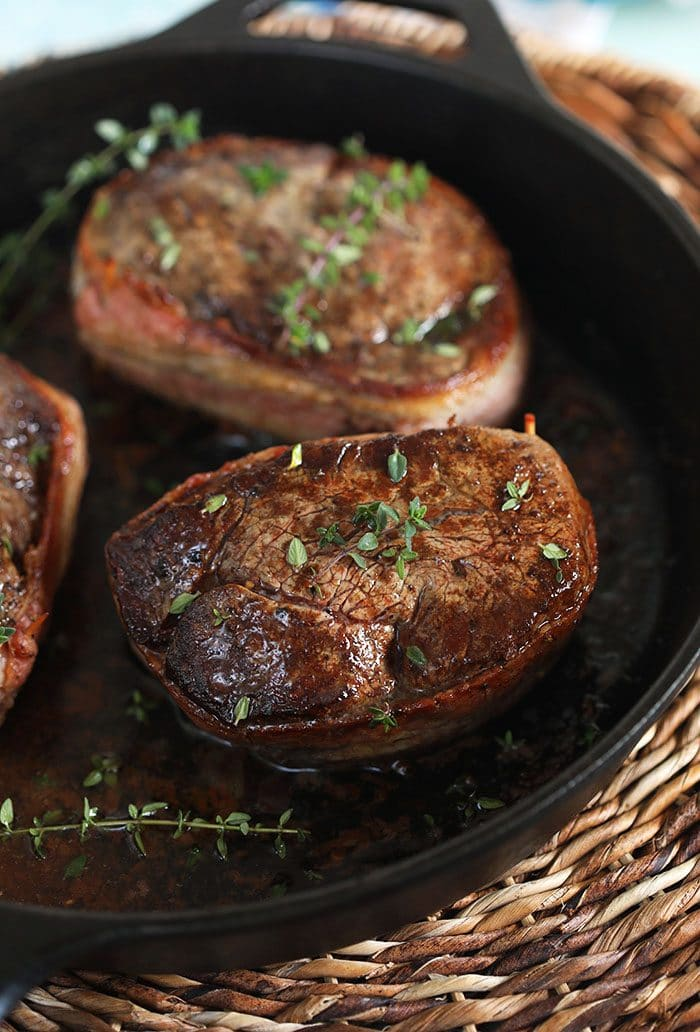 Bacon Wrapped Filet Mignon in a cast iron skillet.