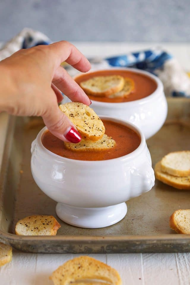 Tomato bisque in a white bowl on a baking sheet with a crouton being placed on top.