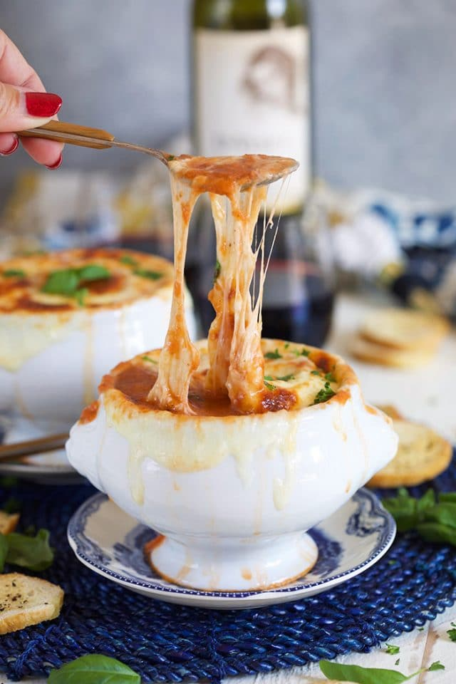 Super cheesy Baked Tomato Bisque with a spoon pulling melty cheese.