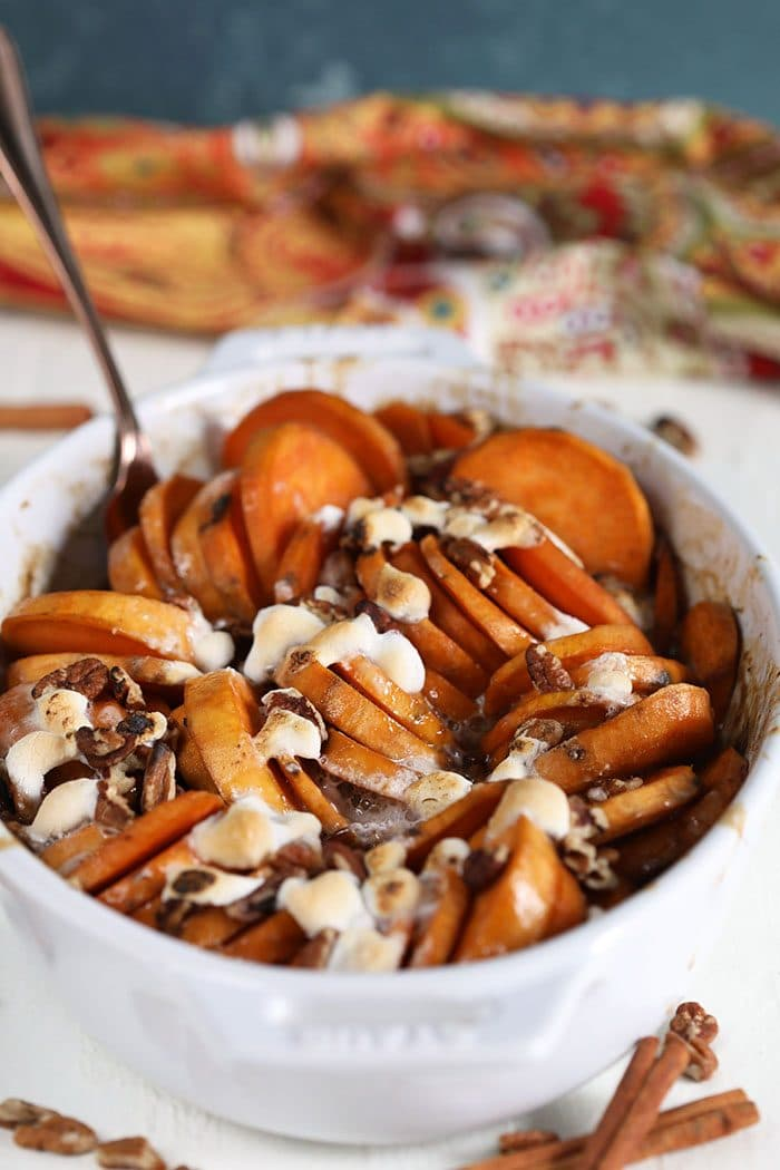 Candied yams in a white casserole dish with a copper serving spoon.