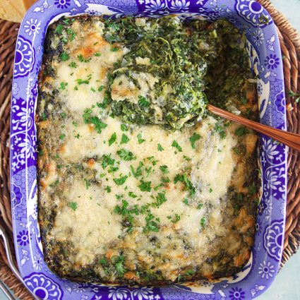 overhead shot of creamed spinach gratin in a blue and white baking dish.