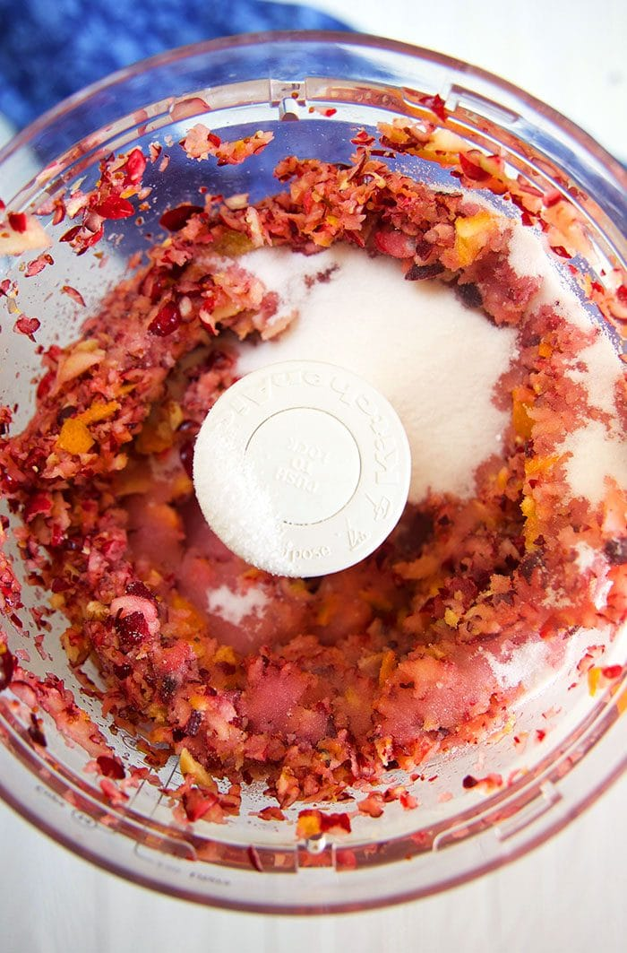 chopped ingredients for cranberry relish in the bowl of a food processor.