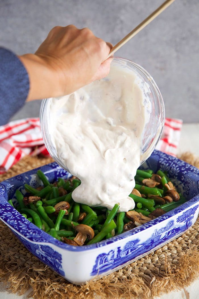 Green bean casserole with cream sauce being poured over top.
