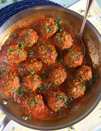 Overhead shot of porcupine meatballs in tomato sauce in a skillet with a spoon.