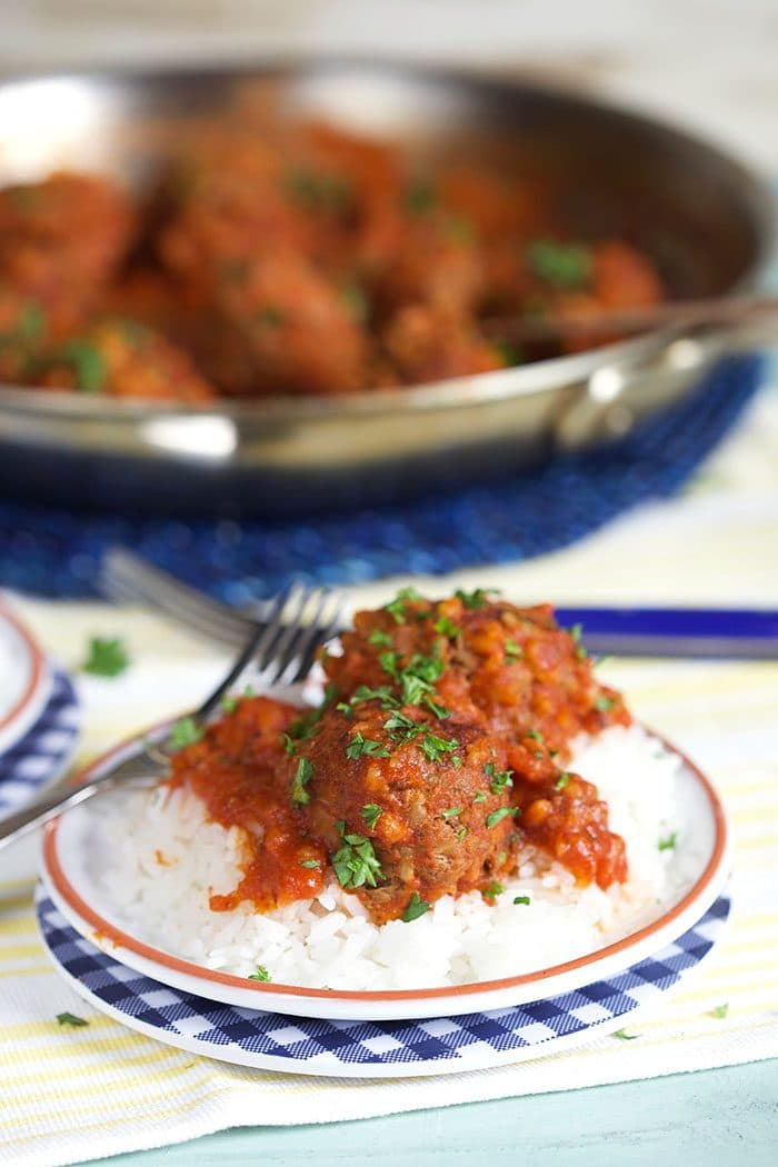 Easy Porcupine Meatballs in red sauce over a bed of rice with a skillet in the background.