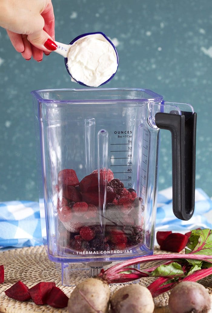 yogurt being added to blender pitcher for berry beet smoothie.