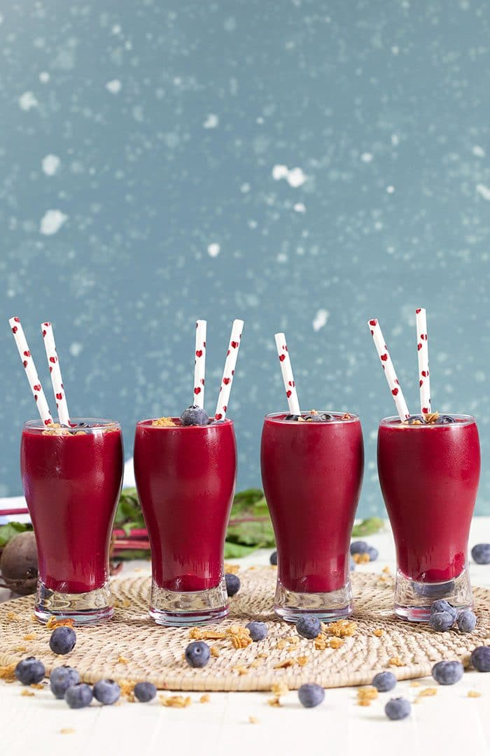 Four berry beet smoothies in a line on a blue background.