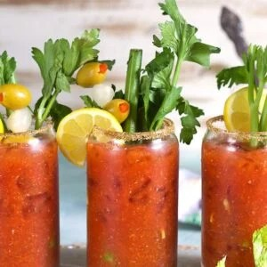 Bloody Mary Mix in a glass with celery and olives.