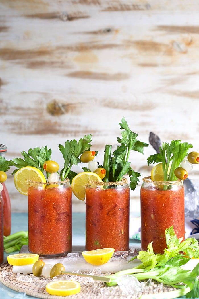 Bloody Mary cocktails lined up on a wicker placemat.