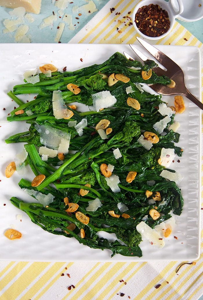Broccoli rabe on a white square platter with crushed red pepper flakes in a bowl.