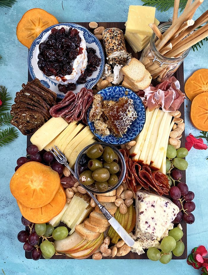 Overhead shot of charcuterie board on a blue background.