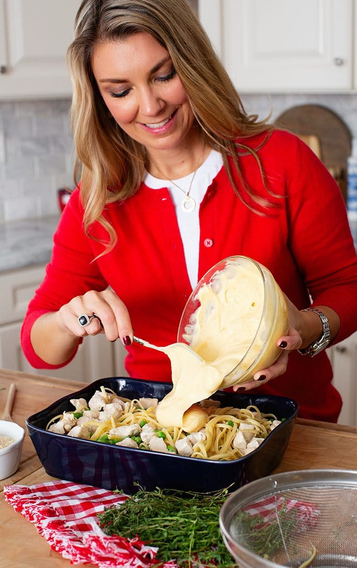 Woman pouring a sauce over pasta.