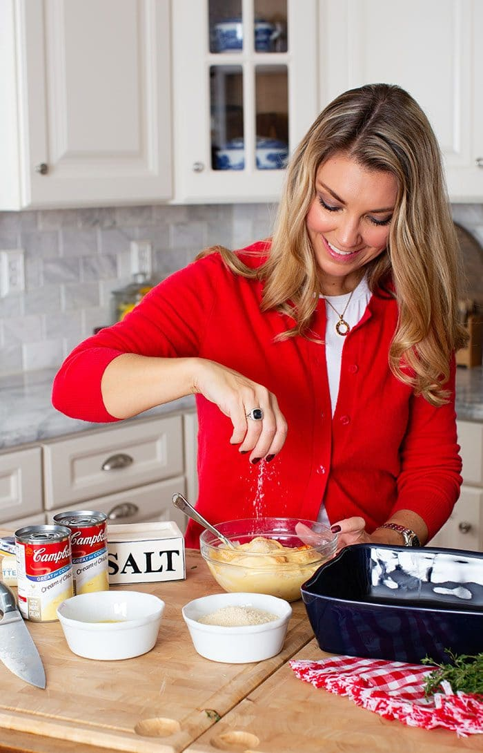 Woman sprinkling salt into a bowl of cream of chicken soup.