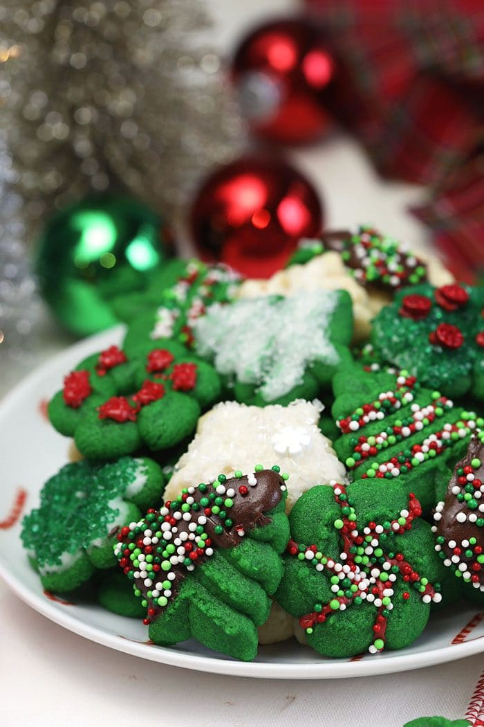 Spritz cookies on a plate with ornaments in the background.