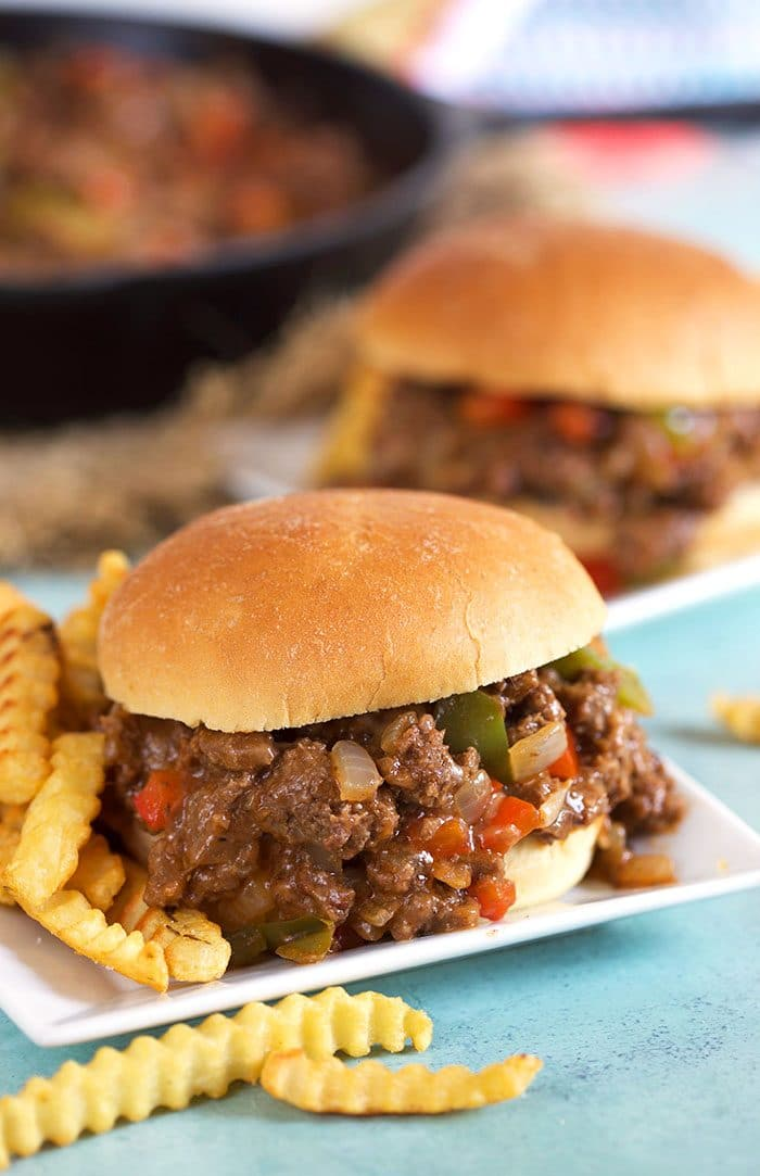 Philly Cheesesteak Sloppy Joe on a white square plate with crinkle cut fries.