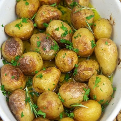 Oven roasted baby potatoes in a white casserole dish.