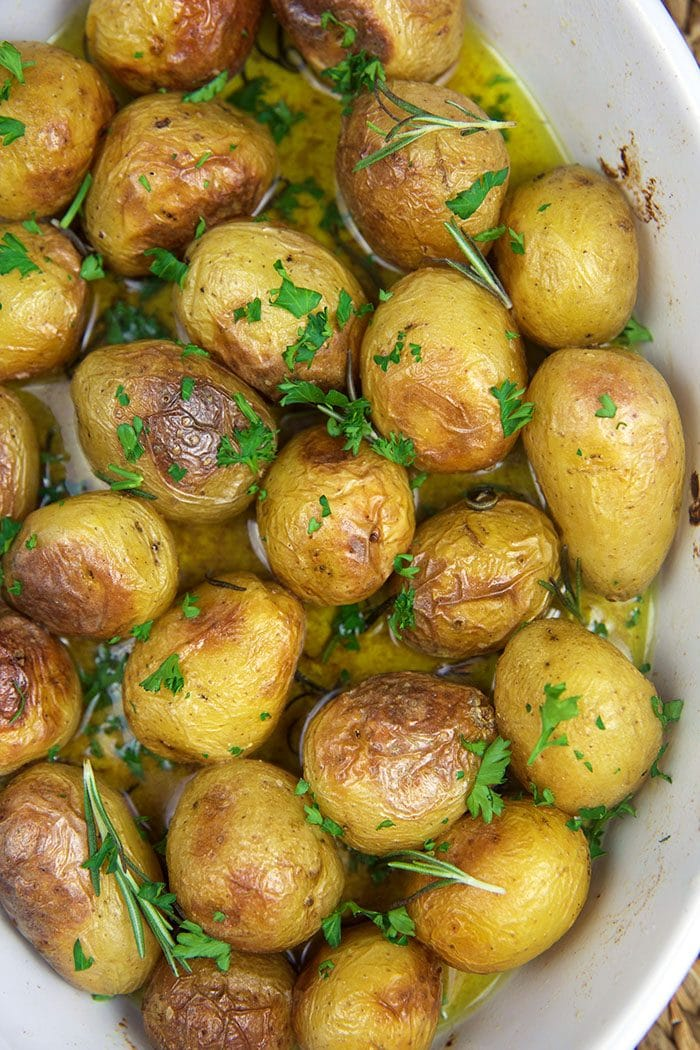 Overhead shot of oven roasted baby potatoes in a white casserole.