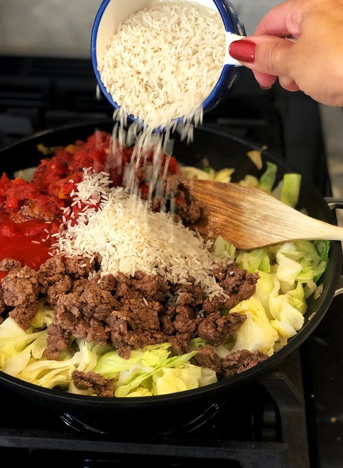 Ingredients for stuffed cabbage casserole with rice being poured on top.