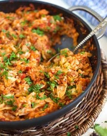 Stuffed cabbage casserole in a skillet with a spoon.