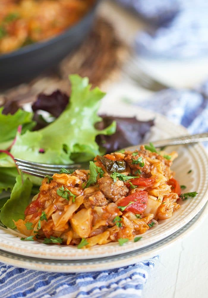 Stuffed cabbage casserole on a white plate with a green salad.