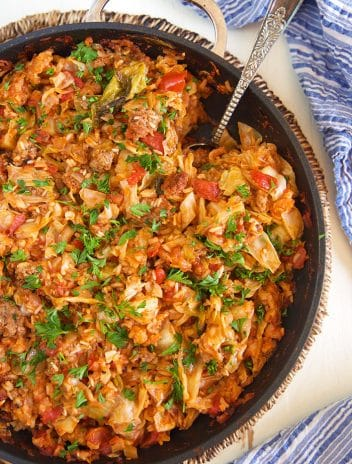 Overhead shot of stuffed cabbage casserole in a black skillet.