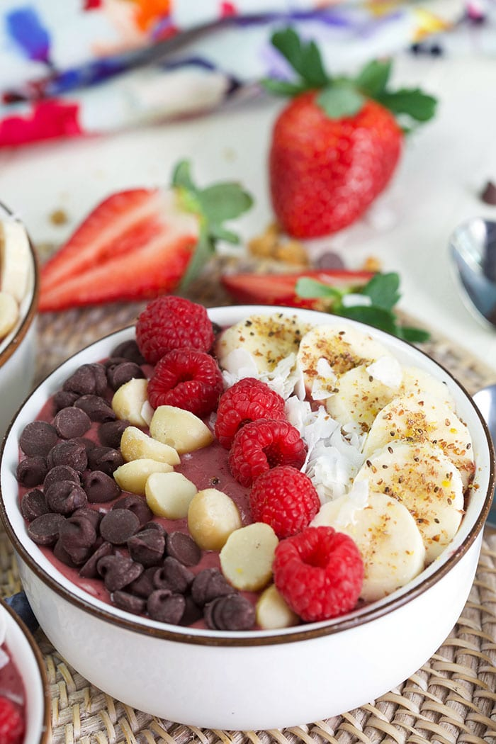 Acai bowl with raspberries, macadamia nuts and chocolate.