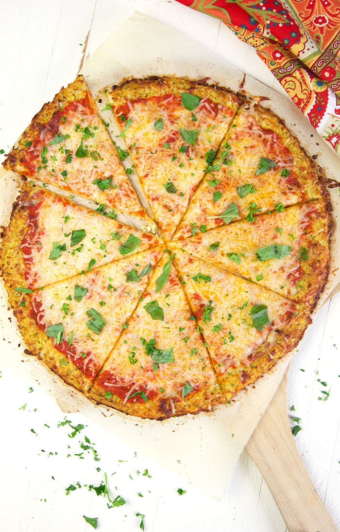 overhead shot of cauliflower pizza on a pizza peel