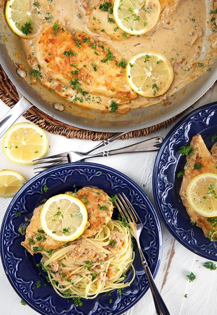 overhead shot of chicken scallopini on a blue plate with a skillet.