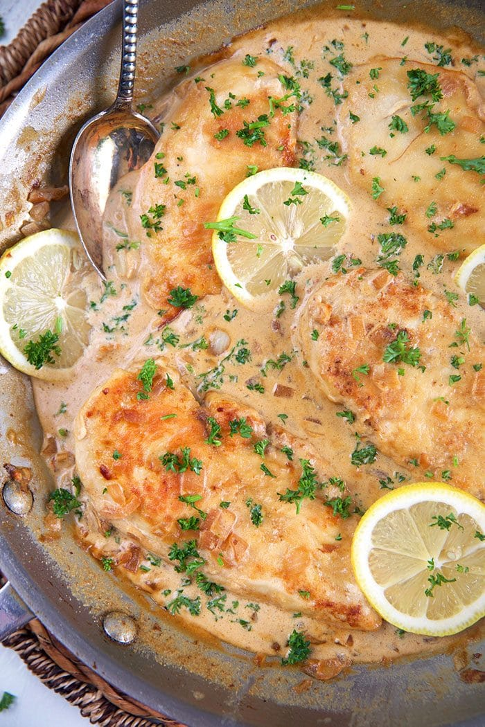 Chicken Scallopini in a skillet with creamy garlic lemon sauce.