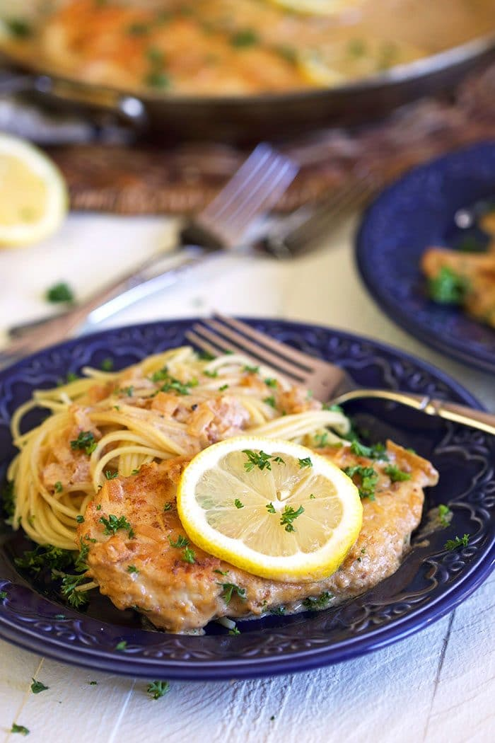 Chicken scallopini on a blue plate with pasta and a lemon slice.