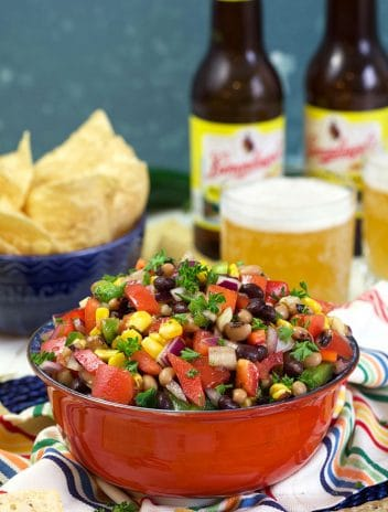 Texas caviar in a red bowl with beer in the background.